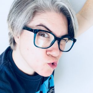 Image is of a non-gendered person wearing glasses while making a strange face.